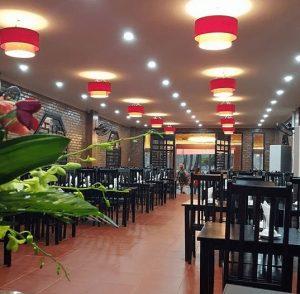 Không gian ấm cúng với tường gạch thô đỏ và ghế gỗ tại nhà hàng Cơm Niêu Nhà Đỏ Đà Nẵng